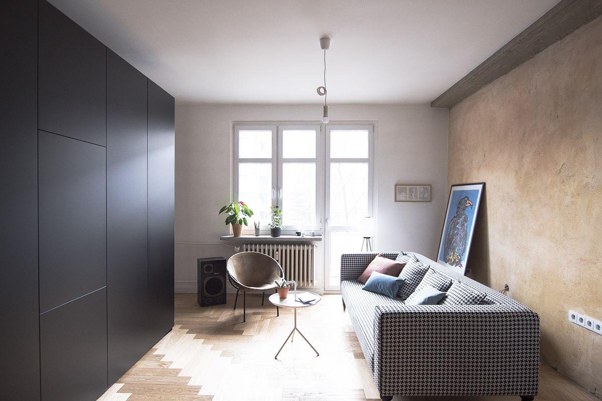 widok na salon z kanapą i czarną zabudową