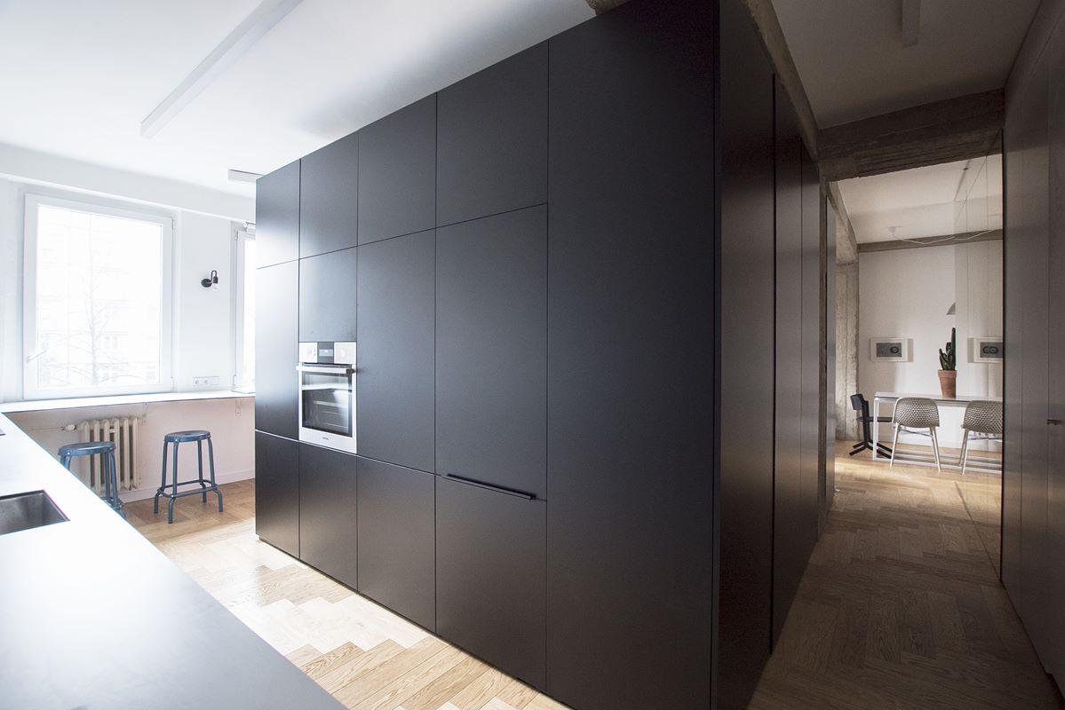 widok na kuchnię i hol czarna zabudowa